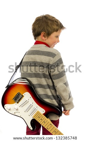 boy with guitar on his back looking over shoulder. - stock photo