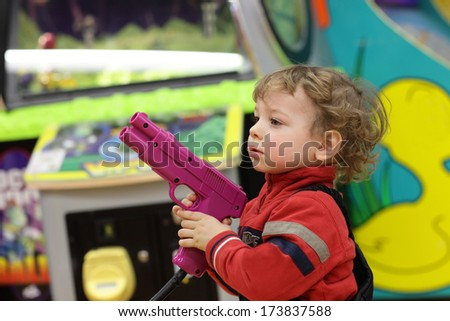 Boy with handgun at an amusement park - stock photo