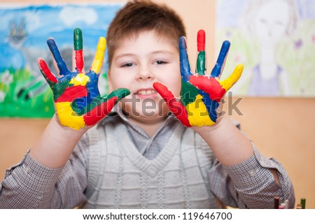 Boy with hands soiled in a paint - stock photo