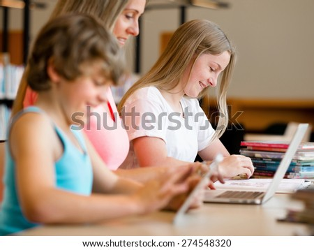 Boy with his famile on background in library with computer - stock photo