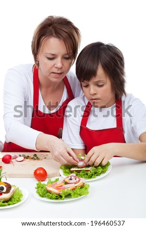 Boy with his mother decorating party sandwiches - isolated