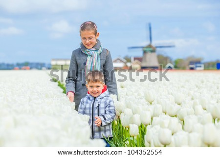 Boy with his sister and grandmother runs between of the purple tulips field