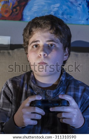 boy with joystick playing computer game at home.