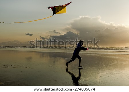 Boy with Kite at sunset on the beach in Newport, Oregon. - stock photo