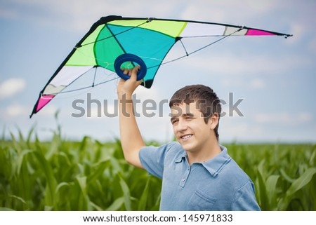 Boy with kite on a corn field