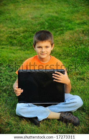 boy with laptop on green grass