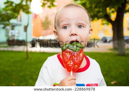 Boy with large lollipop the park - stock photo