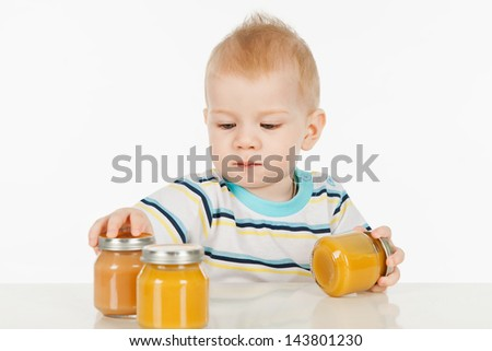 Boy with little jars of baby food, on a gray background - stock photo