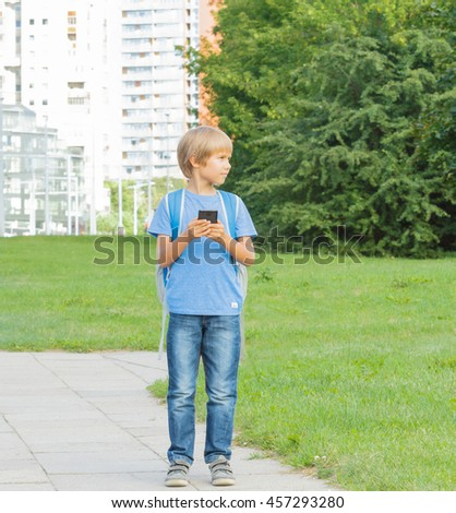 Boy with mobile phone. Child goes in the street and uses touchscreen smartphone. City background. School, technology, leisure concept - stock photo