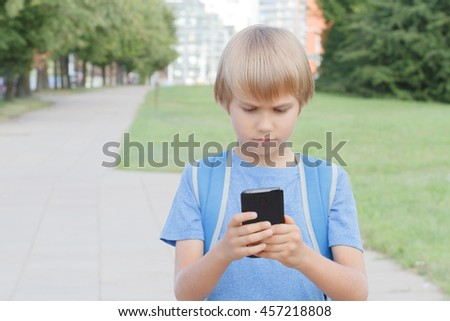 Boy with mobile phone in the street. Child looks at the screen, use apps, plays, writes or reads message. City background. Childhood, school, technology, leisure concept - stock photo