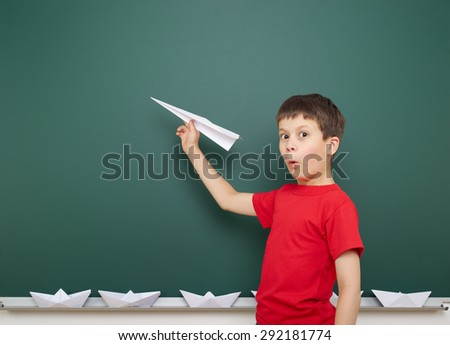boy with origami toy near the school board - stock photo
