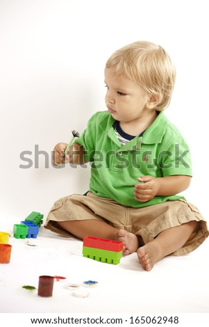 Boy with paints and block