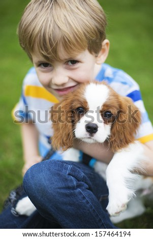 Boy With Pet King Charles Spaniel Puppy - stock photo