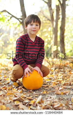 Boy with pumpkin in the Autumn park