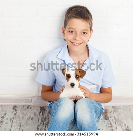 Boy with puppy. Teen with dog at home