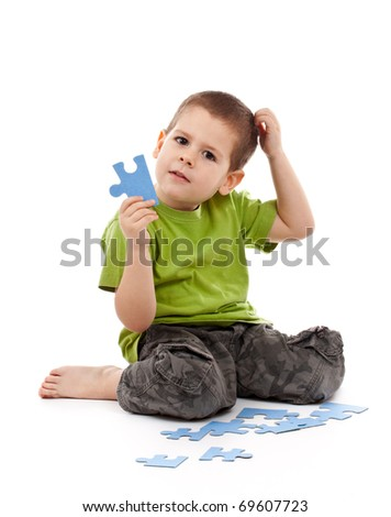 Boy with puzzles scratches his head and thinking