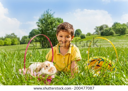 Boy with rabbit and two baskets in the park