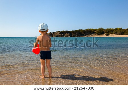Boy with red bucket on beach - stock photo