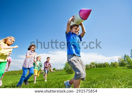 Boy with rocket carton toy and children running