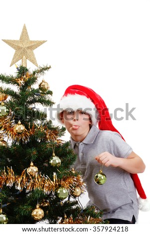 Boy with santa hat sticking out tongue at  the Christmas tree on white background - stock photo