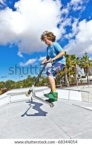 boy with scooter is jumping at the skate park - stock photo