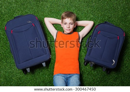 Boy with siutcases th lying on green grass - stock photo