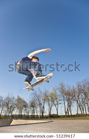boy with skate bard is going airborne at a skate park - stock photo