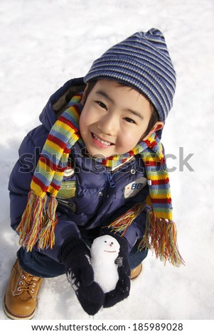 boy with small snowman - stock photo
