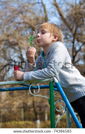 Boy with soap bubbles - stock photo
