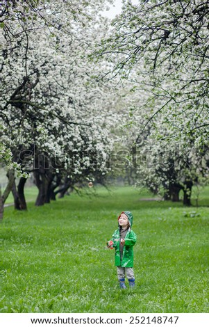 Boy with soap bubbles on blooming apple trees background
