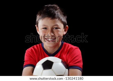 Boy with soccer ball on black background with dramatic lighting style