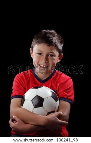 Boy with soccer ball on black background with dramatic lighting style - stock photo