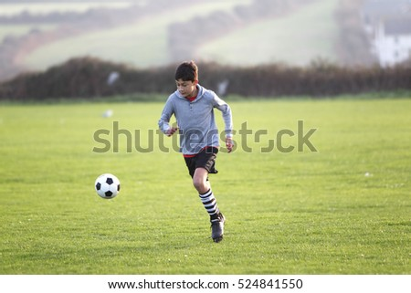 Boy with soccer ball outside in the golden hour near sunset - action
