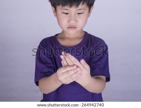 Boy with sore hands and fingers. - stock photo