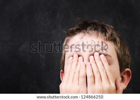 Boy with stupid written on his forehead - stock photo