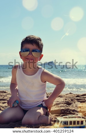 Boy with sunglasses on the beach - stock photo
