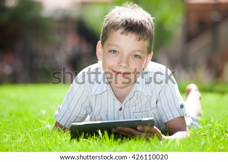 Boy with tablet outdoors. Child with pc computer - stock photo