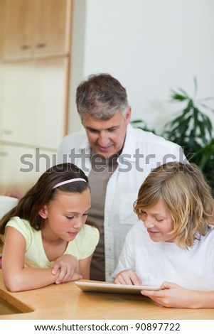 Boy with tablet showing things to his sister and father