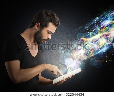 Boy with tablet that emits lighting effects - stock photo