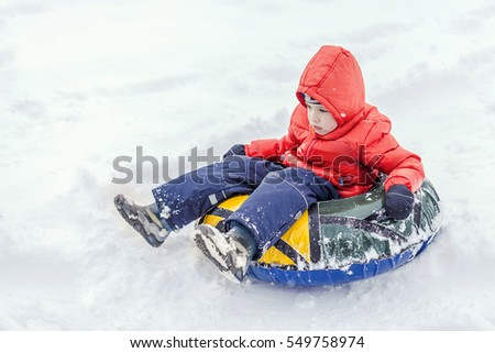 Boy with the inflatable sledge, snow tube, inner tube, lies on snow