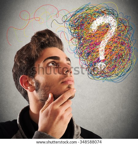 Boy with thoughtful expression and question mark - stock photo
