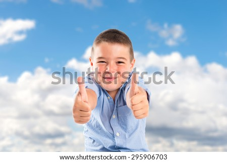 Boy with thumbs up on the floor over clouds background