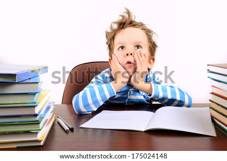 boy with tousled hair sitting at a desk. boy is 5 years. horizontal - stock photo