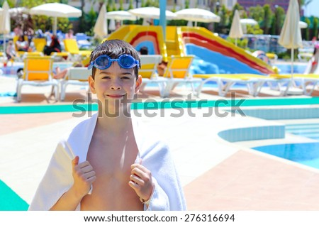 Boy with towel near the pool - stock photo
