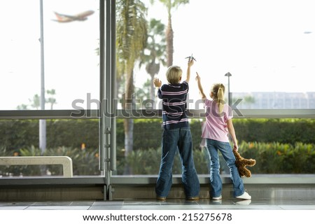 Boy (8-10), with toy plane, and girl , with soft toy, looking through large window in airport departure lounge, watching aeroplane taking off, rear view - stock photo