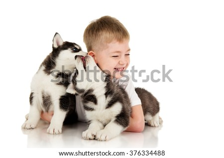 Boy with two husky puppies, isolated on white