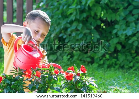 boy with watering can on garden - stock photo