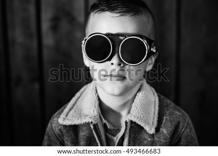 boy with welding glasses,an unusual portrait of the beautiful boy with short hair,black and white photography