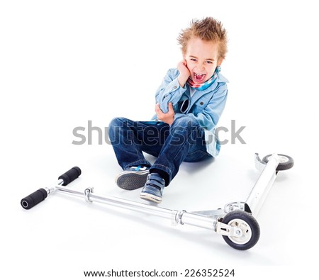Boy with wounded ell crying near by scooter - stock photo