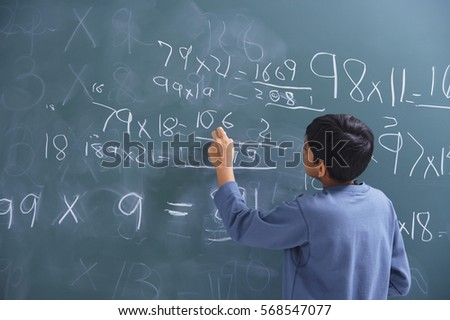 boy working at chalkboard (back view)